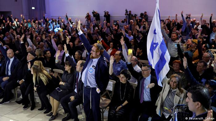 Likud Party members vote via a show of hands at a Likud Central Committee meeting.