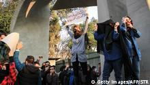 30.12.2017 Iranian students protest at the University of Tehran during a demonstration driven by anger over economic problems, in the capital Tehran on December 30, 2017. Students protested in a third day of demonstrations sparked by anger over Iran's economic problems, videos on social media showed, but were outnumbered by counter-demonstrators. / AFP PHOTO / STR (Photo credit should read STR/AFP/Getty Images)