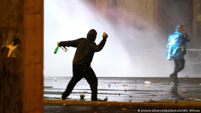Ein Mann wirft in Leipzig-Connewitz Flaschen nach einem Wasserwerfer der Polizei