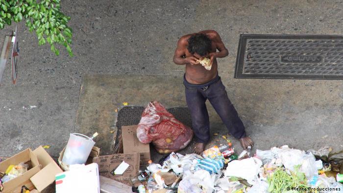 Homem procura comida em lixo em Caracas
