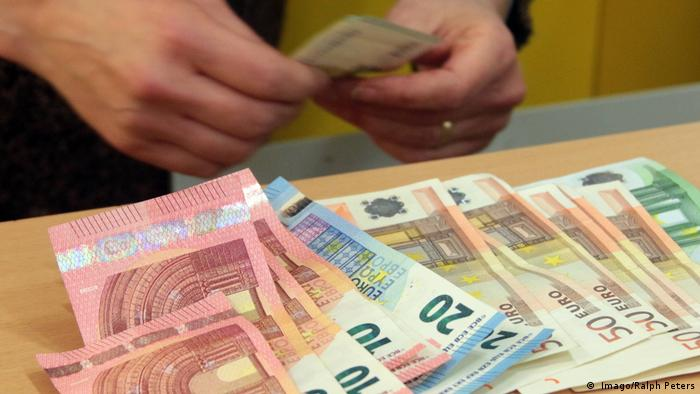 Person counting euro banknotes ( Imago/Ralph Peters)