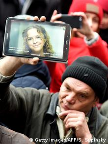 A protester holds up a digital device showing the picture of Nozdrovska