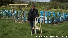 TO GO WITH FEATURE BY ROBIN MILLARD Artist and furniture maker Gavin Munro stands with an early prototype chair in front of trees growing around their specially constructed frames to produce items of furniture at his 'Full Grown' plantation site near Wirksworth, central England, on April 28, 2015. Deep in the English countryside, there's a bizarre sight: rows of trees being grown into upside-down chairs, slowly taking shape over years of careful nurturing. Around 150 armchairs, 100 lampshades and other items including mirror frames are being grown out of the ground in a highly unusual adventure in furniture design. The brainchild of Gavin Munro, his Full Grown company has produced some early prototypes, with each item one solid, joinless piece of wood. AFP PHOTO / OLI SCARFF (Photo credit should read OLI SCARFF/AFP/Getty Images)