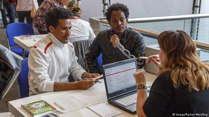 Two Eritrean men consult with a woman at a desk at a job centre for migrants in Germany