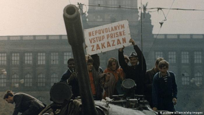 People stand on top of a Soviet tank holding a sign that reads: 'Unauthorized access strictly forbidden'