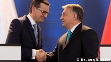 Polish Prime Minister Mateusz Morawiecki (R) and Hungarian Prime Minister Viktor Orban (L) shake hands during a joint news conference in Budapest (Reuters/B. Szabo)