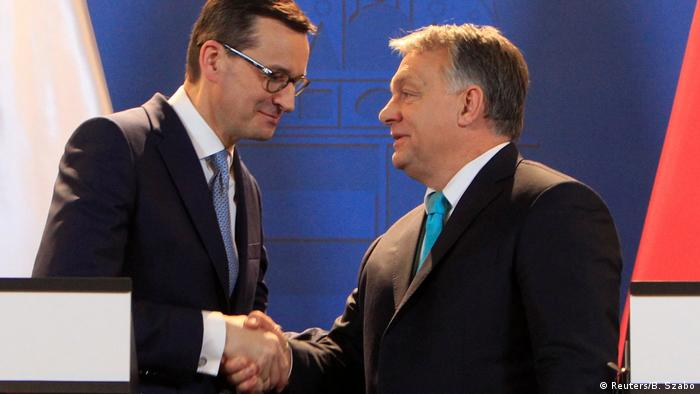 Polish Prime Minister Mateusz Morawiecki (R) and Hungarian Prime Minister Viktor Orban (L) shake hands during a joint news conference in Budapest