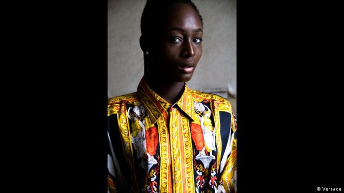 Ein schwarzes Model in farbigem Frauenhemd von Versace in Gold, Rot und Blau.