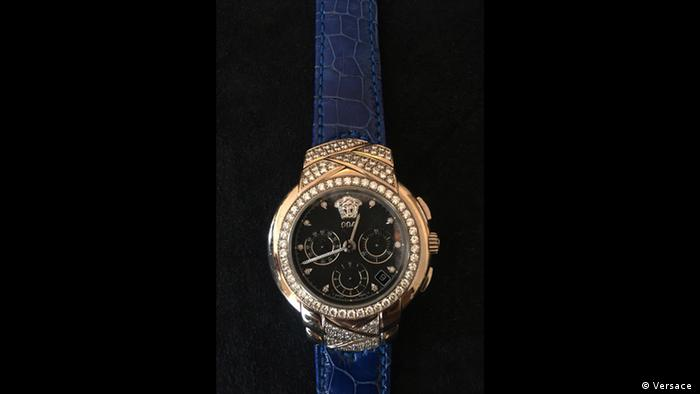 Uhr mit dunklem Ziffernblatt und goldener goldener Fassung von Versace.
