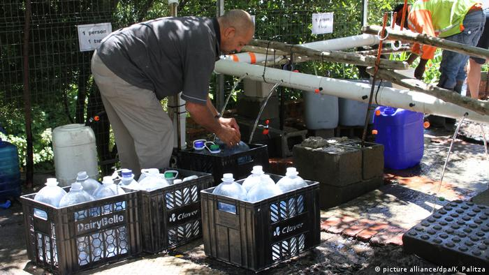 A man fills plastic bottles with water