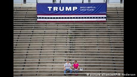 Dos personas bajo un cartel de Trump