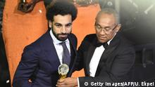 04.01.2018 Confederation of African Football (CAF) President Ahmad Ahmad (R) presents The African Footballer of the Year Award to Egypt and Liverpool striker Mohamed Salah during an award ceremony at the International Conference Centre in Accra on January 4, 2018. / AFP PHOTO / PIUS UTOMI EKPEI (Photo credit should read PIUS UTOMI EKPEI/AFP/Getty Images)