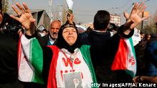 5.1.2018*** An Iranian woman wearing a portrait of Supreme leader Ayatollah Ali Khamenei around her neck and the colours of the national flag shouts slogans during a pro-government march held after the weekly Friday prayers in central Tehran on January 5, 2018. New pro-regime protests were held in Iran, in reaction to the protests against the government and the cost of living. / AFP PHOTO / ATTA KENARE (Photo credit should read ATTA KENARE/AFP/Getty Images)