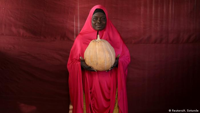 Eine lächelnde Frau hält einen großen Kürbis mit beiden Händen (Foto: Reuters)