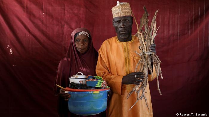 Eine Frau mit einer Schüssel und ein Mann mit einem Holzbündel vor einem roten Tuch (Foto: Reuters)