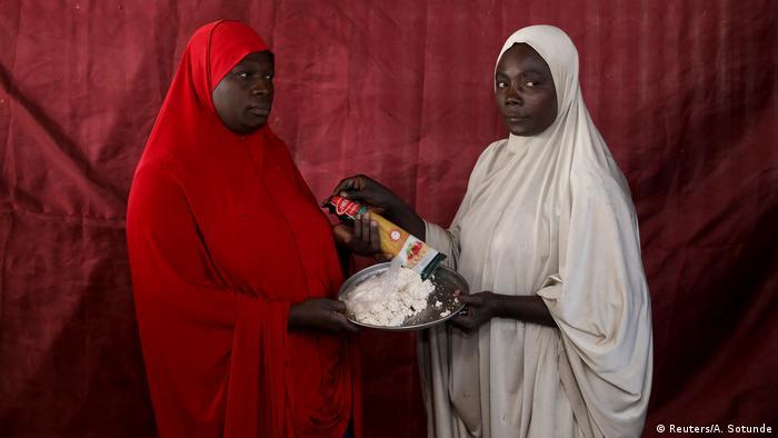 Zwei Frauen überreichen sich gegenseitig eine Packung Spaghetti und ein tablett mit einer weißlichen Paste (Foto: Reuters)
