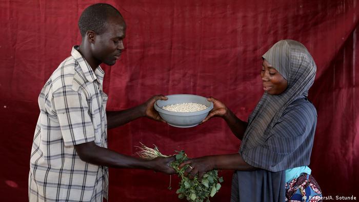 Ein Mann und eine Frau stehen sich gegenüber und tauschen eine Schüssel gegen Blätter (Foto: Reuters)
