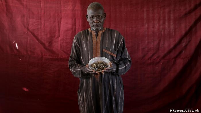 Ein Mann hält eine kleine Schüssel mit Trockenfisch in die Kamera (Foto: Reuters)