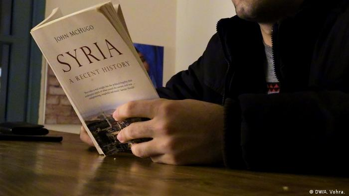 Sami reads a book on Syria in a Beirut café