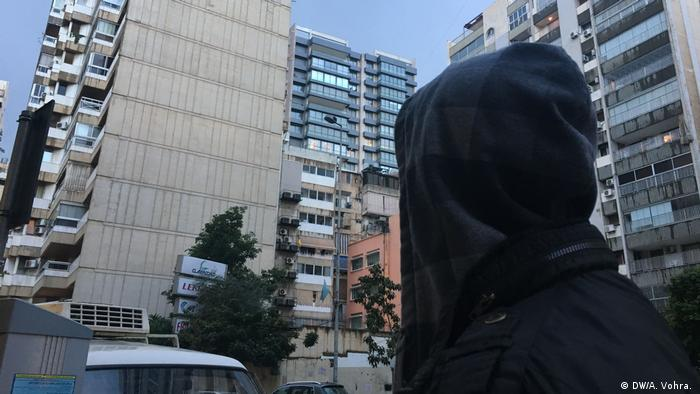 Bassam walks past tower blocks in Beirut