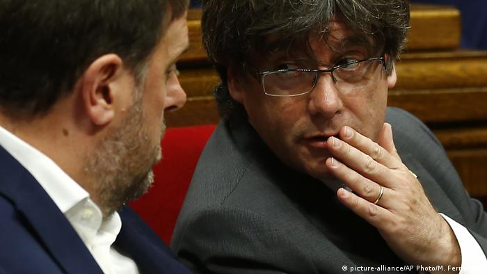 Catalonian Vice President Oriol Junqueras listens as Catalan President Carles Puigdemont speaks to him with his hand over his mouth.
