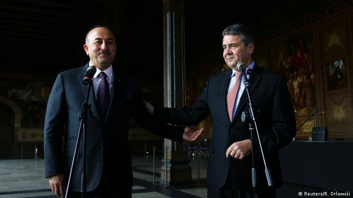 German Foreign Minister Sigmar Gabriel pats Turkish Mevlut Cavusoglu on the arm during press conference