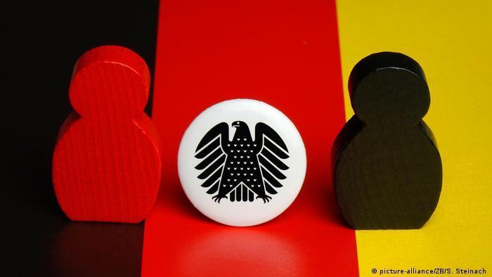 Figuren und Bundesadler auf einer Deutschlandfahne (picture-alliance/ZB/S. Steinach )
