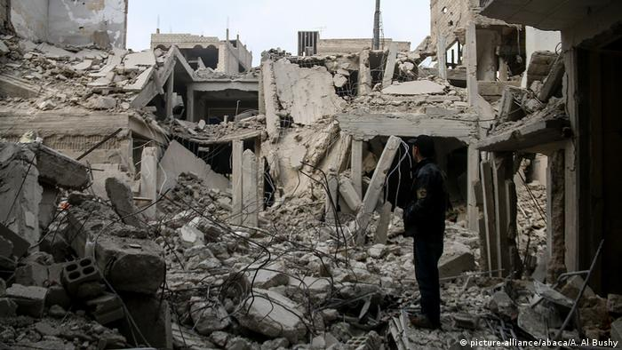 A man looks at the wreckage of collapsed buildings after Assad regime airplanes carried out an airstrike on the besieged town of Arbin