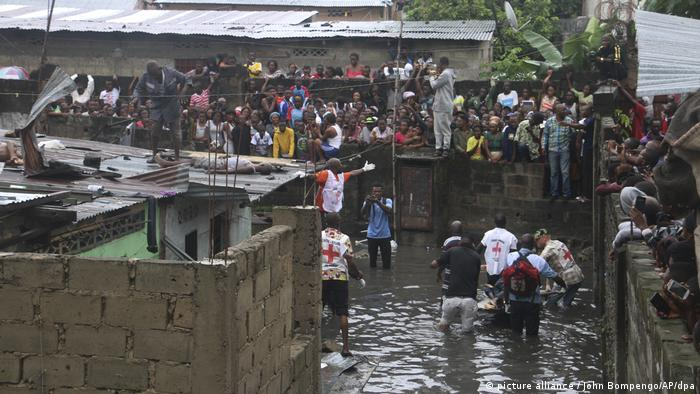 People threading through water in a flooded street in Kinshasa