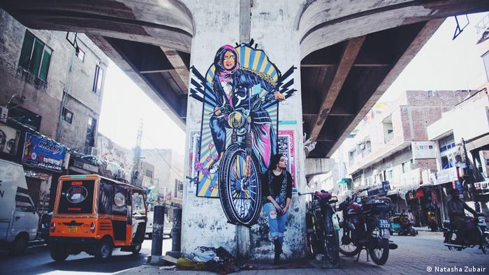 Fashion model Eman Suleman poses in front of graffiti done by Shehzil Malik under a bridge in Lahore, Pakistan (Natasha Zubair)