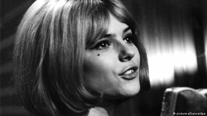 France Gall sings into microphone in 1965.