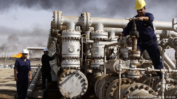 Iraqi laborers work at an oilfield near Basra