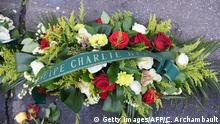A wreath laid in commemoration of the victims of the jihadist attack on French satirical magazine Charlie Hebdo is pictured near the magazine's offices in Paris on January 7, 2018, on the third anniversary of the attack. Two French jihadists who had sworn allegiance to al-Qaeda killed 11 people at Charlie Hebdo's offices in 2015 over the staunchly atheist magazine's satirical coverage of Islam and the prophet Mohammed. / AFP PHOTO / CHRISTOPHE ARCHAMBAULT (Photo credit should read CHRISTOPHE ARCHAMBAULT/AFP/Getty Images)