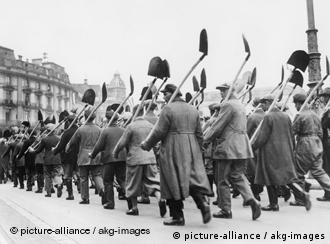 Workers marching to work on building an autobahn, shovels on their shoulders