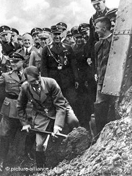 Der nationalsozialistische Führer und Reichskanzler Adolf Hitler beim ersten Spatenstich zum Bau der Reichsautobahn in Frankfurt am Main. Mit den Bauarbeiten an den Straßen des Führers wurde am 23. September 1933 begonnen. Am 19. Mai 1935 wurde im Beisein einer riesigen Zuschauermenge das erste Teilstück der Reichsautobahn Frankfurt-Heidelberg durch Hitler übergeben. Das Projekt Reichsautobahn diente neben der Verbesserung der Infrastruktur des Straßenverkehrs der Arbeitsbeschaffung und somit der Ankurbelung der Wirtschaft. Auch militärstrategische Gesichtspunkte spielten für den raschen Ausbau der innerdeutschen Verkehrswege eine große Rolle.