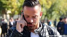 ARCHIV - Der Fußballprofi und ehemalige FC St.-Pauli-Spieler Deniz Naki telefoniert während er am 08.11.2016 das Gericht im südosttürkischen Diyarbakir, Türkei verlässt. Naki ist wegen «Terrorpropaganda» zu einer Bewährungsstrafe von einem Jahr, sechs Monaten und 22 Tagen verurteilt worden. Die Bewährungszeit betrage fünf Jahre, sagte Nakis Anwalt Soran Haldi Mizrak der Deutschen Presse-Agentur. zu dpa Fußballprofi Deniz Naki in Türkei zu Bewährungsstrafe verurteilt am 06.04.2017) Foto: Str/EPA/dpa +++(c) dpa - Bildfunk+++ |