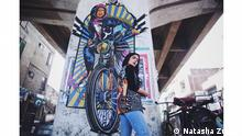 Shehzil Malik stands in front of her graffitti depicting a Pakistani girl on a morotcycle (Natasha Zubair)