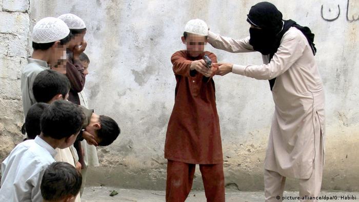 Ein IS-Mitglied trainiert einen Jungen im Umgang mit einer Waffe (Foto: picture-alliance)