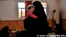 TOPSHOT - The wife of a suspected member of the Islamic State (IS) group holds her child as she waits on the western frontline to be questioned after fleeing the centre of Raqa, on October 8, 2017. Syrian Democratic Forces (SDF), Syrian fighters backed by US special forces, are battling to clear the last remaining jihadists holed up in their crumbling stronghold of Raqa. / AFP PHOTO / BULENT KILIC (Photo credit should read BULENT KILIC/AFP/Getty Images)