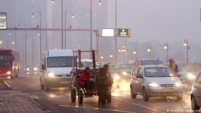 Vehicles and pedestrians are seen during evening fog and air pollution covering Skopje