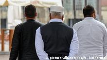 Eine Gruppe muslimischer Männer geht ü+ber den Marktplatz in der Hansestadt Bremen. Foto: Winfried Rothermel | Verwendung weltweit