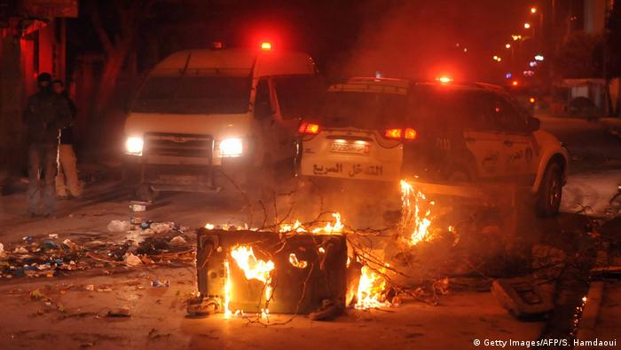 Police vehicles surround burning objects following protests in Tunis