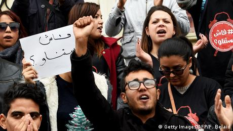 Tunisian protestors hold signs denouncing price hikes in Tunis