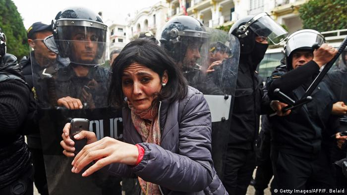 A woman stands in front of Tunisian police in Tunis (Getty Images/AFP/F. Belaid)