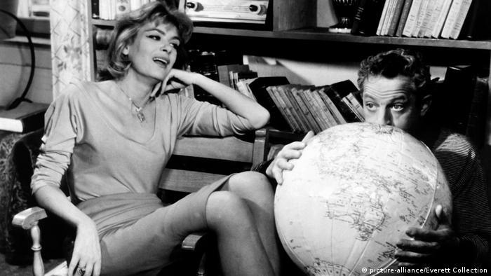 Melina Mercouri in sitzt im Film Sonntags nie auf einem Stuhl und lacht, ein Mann neben ihr bläst einen Wasserball in Form einer Weltkugel auf. (picture-alliance/Everett Collection)