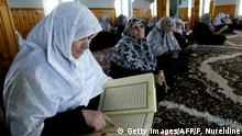 17.10.2003 KOMOTINI, GREECE: TO GO WITH AFP STORY BY CATHERINE BOITARD (Grece-minorites-femmes-Turquie-Islam)..Women belonging to Greece's muslim minority read from the Qora'an holy muslim book, in a mosque in Komotini, northeastern Greece 17 October 2003. Some 100,000 muslims live in Greece's border region with Turkey and Bulgaria demand an improvement in their education and social rights. AFP PHOTO/ FAYEZ NURELDINE (Photo credit should read FAYEZ NURELDINE/AFP/Getty Images)