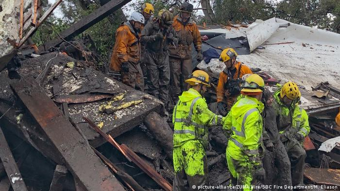 Firefighters assist a girl out of a collapsed muddy structure (picture-alliance/ZUMA Wire/SBC Fire Department/M. Eliason)