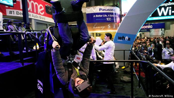 A showgoer tries out the Flying Dino ride using a Samsung VR headset at CES in Las Vegas. (Reuters/R. Wilking)
