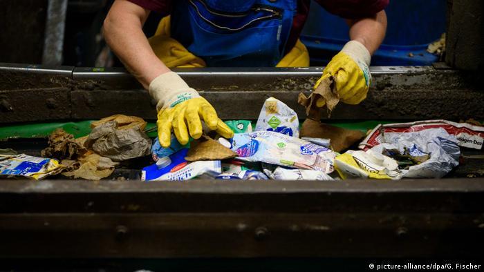 Eine Person trennt Müll per Hand in einer Sortieranlage