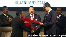 Director General of Civil Aviation Malaysia, Azharuddin Abdul Rahman, left, shakes hand and exchanges the Memorandum of Understanding documents with CEO of Ocean Infinity Limited, Oliver Plunkett, right, during the signing ceremony of the MH370 missing plane search operations between Malaysian government and Ocean Infinity Limited in Putrajaya, Malaysia, Wednesday, Jan. 10, 2018. (AP Photo/Sadiq Asyraf) |